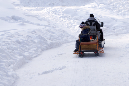 a man riding on a snowmobile with the kids