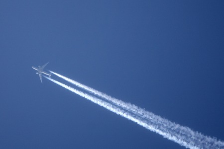 White trace of plane across the blue sky. Jet airplane is flying high Imagens