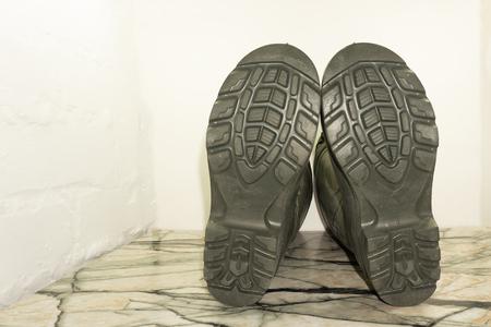 Ansicht von unten auf die Sohle aus dunkelblauem Leder, wasserdicht, winterisoliert, männlicher hoher Stiefel mit Schnallen und Kunstpelzisolierung, isoliert auf Weiß. Standard-Bild