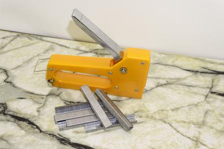 Large stapler and staples for construction work on white