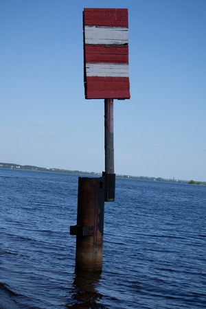 Red and white sign for ships which means no entry on this side at river Hollandsche IJssel in Gouda, the Netherlands