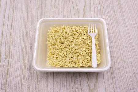 Instant noodles in a plate on a black background. Fast food, junk food, unhealthy food. Rolton. Doshirak