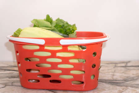 Photo of a wire shopping basket full of fresh fruit and vegetables, isolated on a white background