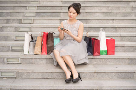 asian girl with shopping bags checking her phone