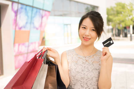 asian girl with shopping bags holding credit card Banco de Imagens