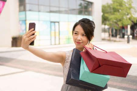 asian girl with shopping bags taking selfie Banco de Imagens