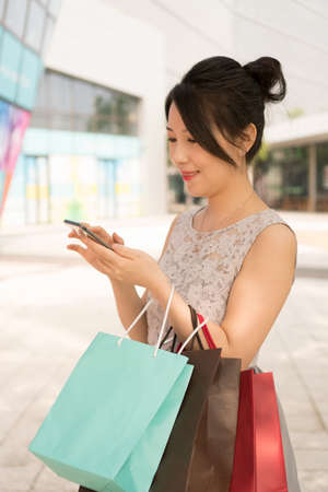 asian girl with shopping bags looking at her phone