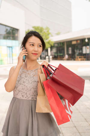 asian girl with shopping bags talking on the phone Banco de Imagens