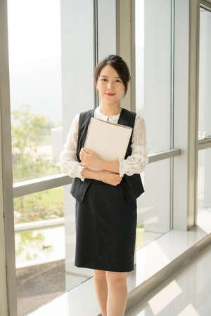 A lady in office wear standing next to a window Banco de Imagens