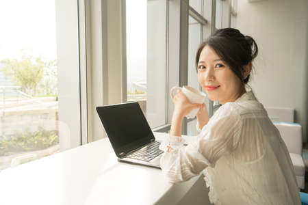 office lady sitting in front of a laptop next to a window