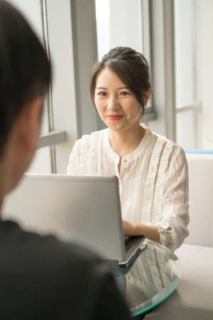 office lady sitting in front of a laptop with a man