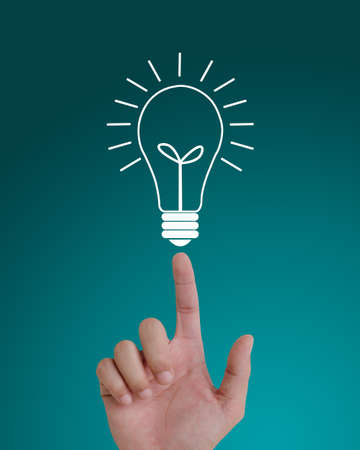 hand pointing to idea light bulb on top. photo