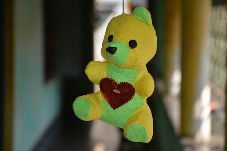 A stuffed doll of teddy bear hanging Imagens