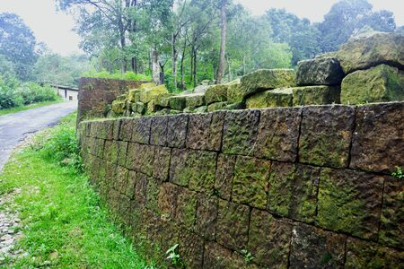 Close up of a mossy cut stone wall on the side of a paved road with trees and grasses in Meghalaya