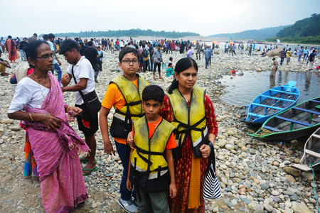 Dawki, Shillong, Meghalaya, 16 June, 2019: Tourists with life jacket ready to board the boat at Dawki river of Shillong, Meghalaya, Bangladesh border with lots of tourists and boat in the background