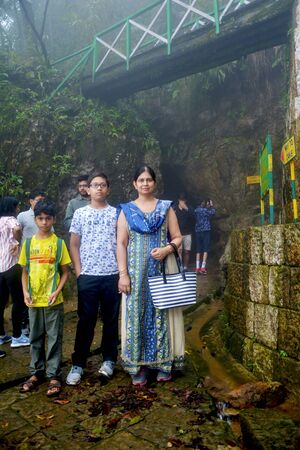 An Indian family consisting of mother daughter and sons posing in front of the caves of Cherrapunjee Ecological Project know known as Sohra Plateau of Meghalaya, Shillong