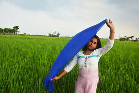 Close up of  a teenage girl wearing white cotton salwar and holding blue dhupatta above her head in a paddy field, selective focusing