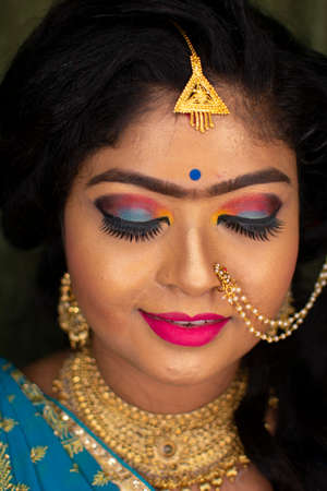 an indian teenage girl happy with indian ethnic wear and ornaments in a marriage reception party Standard-Bild