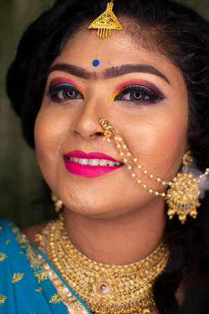an indian teenage girl happy with indian ethnic wear and ornaments in a marriage reception party