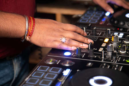 the hands of a DJ on equipment and vinyl record at party