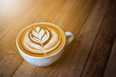 A white cup of coffee latte or cappuccino art on wood table