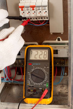 voltmeter: Electrician checking fuse box with a digital voltmeter