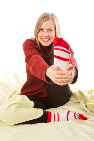 Beautiful young woman smiling and holding her foot  photo