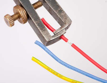 plier: Stripping a red cable with a wire stripper plier