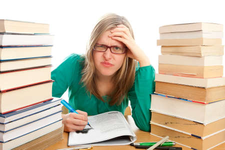 angry blonde: Blond girl learning surrounded by bunch of books  Stock Photo