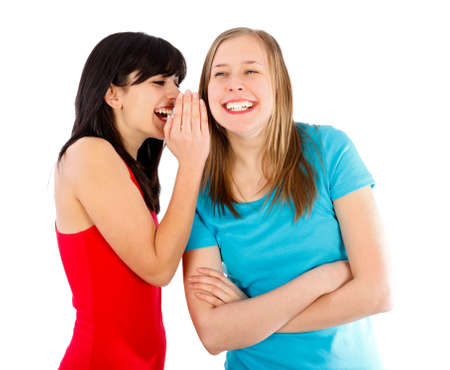 people laughing: Brunette whispering something funny to her blond friend