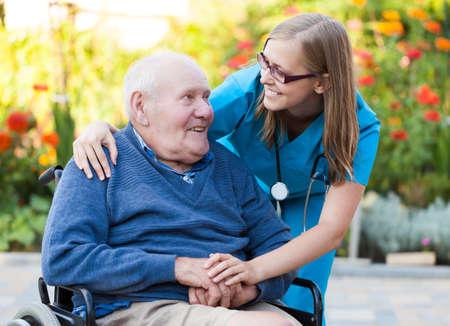 車椅子の老人の世話をして親切なお医者