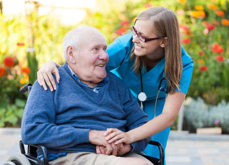 old man: Kind doctor taking care of an old man in wheelchair  Stock Photo