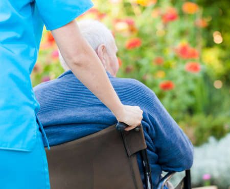 care at home: Young female doctor pushing and old patient in wheelchair  Stock Photo