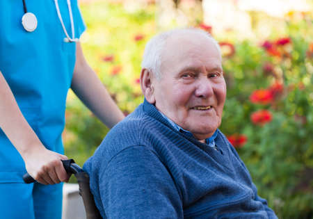 old age care: Happy old patient sitting in wheelcharis, in the garden