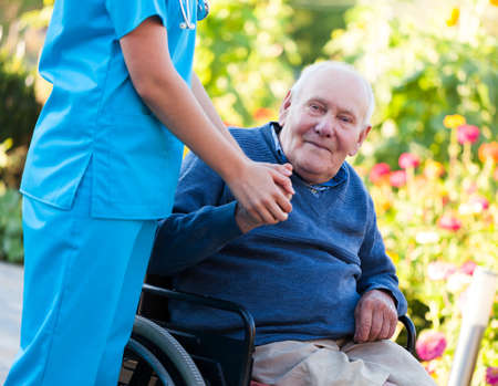 Old patient sitting in wheelchair, holding the doctor Stock Photo