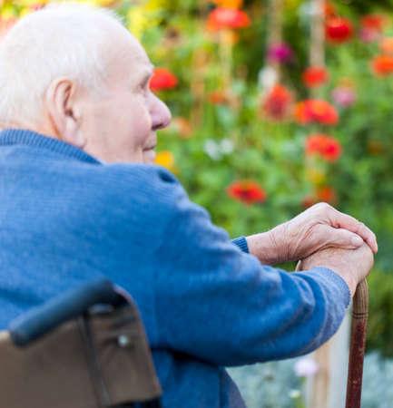 Old man sitting alone in a wheelchair out in the garden  Standard-Bild
