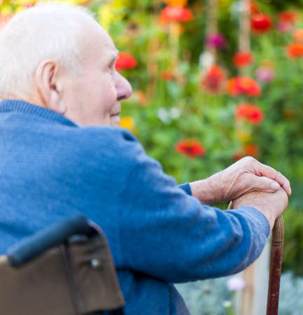 senior care: Old man sitting alone in a wheelchair out in the garden  Stock Photo