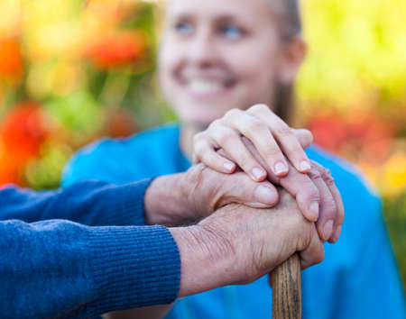 old carer: Young female doctor holding his patient hand  Stock Photo