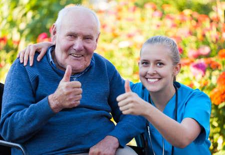 hombre viejo: M�dico joven feliz mostrando los pulgares para arriba con su paciente anciano Foto de archivo