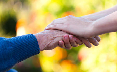 needy: Young female hand holding an old man Stock Photo