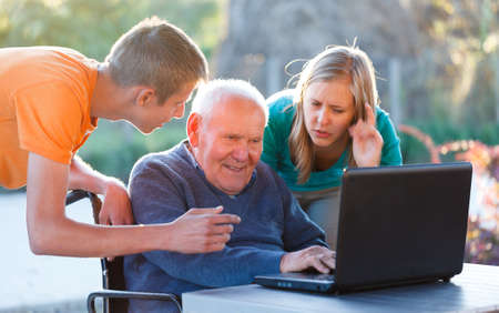 Old grandfather learning how to use modern technology. Stock Photo