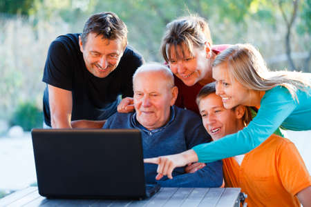 father teaching daughter: Teaching grandfather how to use a laptop.