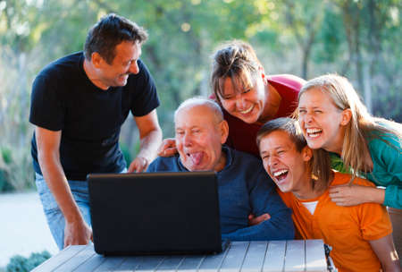 Family laughing together at the funny grandfather. Standard-Bild