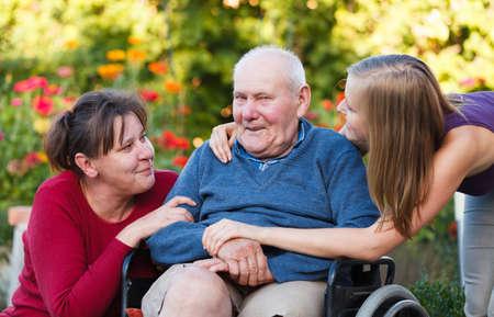 De vrouwelijke generatie bezoek aan oude grootvader in het verpleeghuis