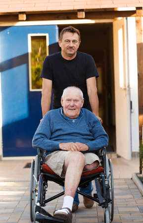 sick person: Old father being pushed in his wheelchair by his son  Stock Photo
