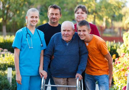 personas enfermas: Familia visitando abuelo en el hogar de ancianos, ayud�ndole con el caminante Foto de archivo