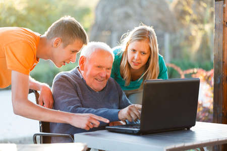 Grandchildren helping their grandfather to use the laptop