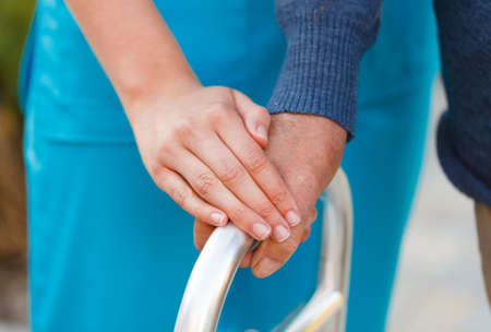 Closeup of a female hand holding an old man Stock Photo