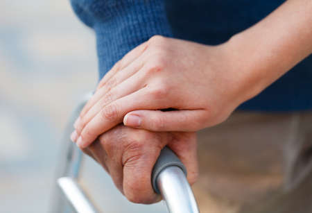 holding close: Giving support to an old man, using the walker