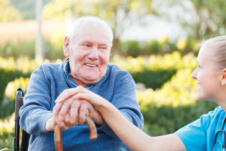 needs: Young happy doctor giving support to his elderly patient  Stock Photo